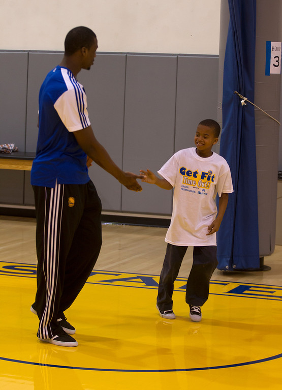 . Nine-year-old Jesse Sexton of Oakland, Calif., right, gets a congratulatory handshake from Golden State Warriors forward Harrison Barnes after a basketball clinic at the Warriors practice facility in downtown Oakland, Calif., Wednesday, Jan. 30, 2013. The Warriors and Kaiser Permanente hosted the event as part of the NBA FIT Live Healthy Week. (D. Ross Cameron/Staff)