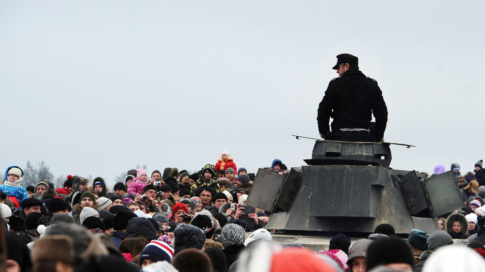 . People crowd near a World War II re-enactor dressed as a  Nazi Germany troops soldier sitting atop his tank after a staged battle to mark the 70th anniversary of the final raise of the Nazi blockade of the city of Leningrad, now St. Petersburg,  in the village of Porogki in Leningrad region, on January 26, 2014. The German and Finnish siege and blockade of Leningrad was broken on January 18, 1943 but finally lifted a year after, on January 27, 1944. The city\'s name was changed back from Leningrad to St. Petersburg after the 1991 Soviet collapse. (OLGA MALTSEVA/AFP/Getty Images)