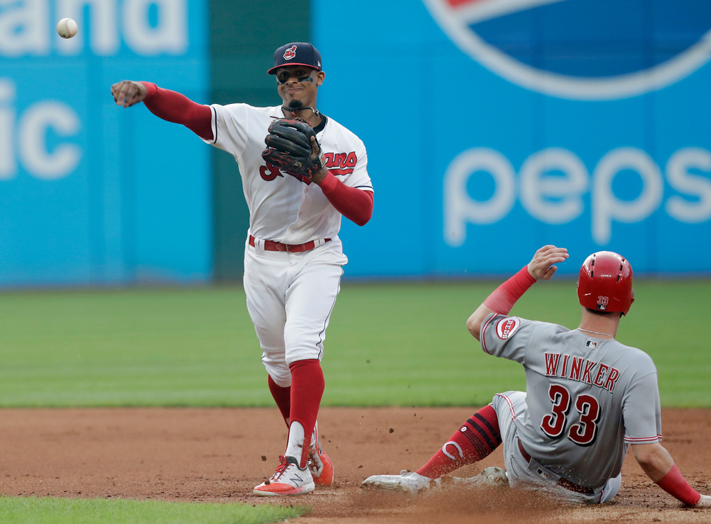 . Cleveland Indians\' Francisco Lindor, left, throws to first base after getting Cincinnati Reds\' Jesse Winker out at second base during the fifth inning of a baseball game, Tuesday, July 10, 2018, in Cleveland. Tucker Barnhart was out at first base for the double play. (AP Photo/Tony Dejak)