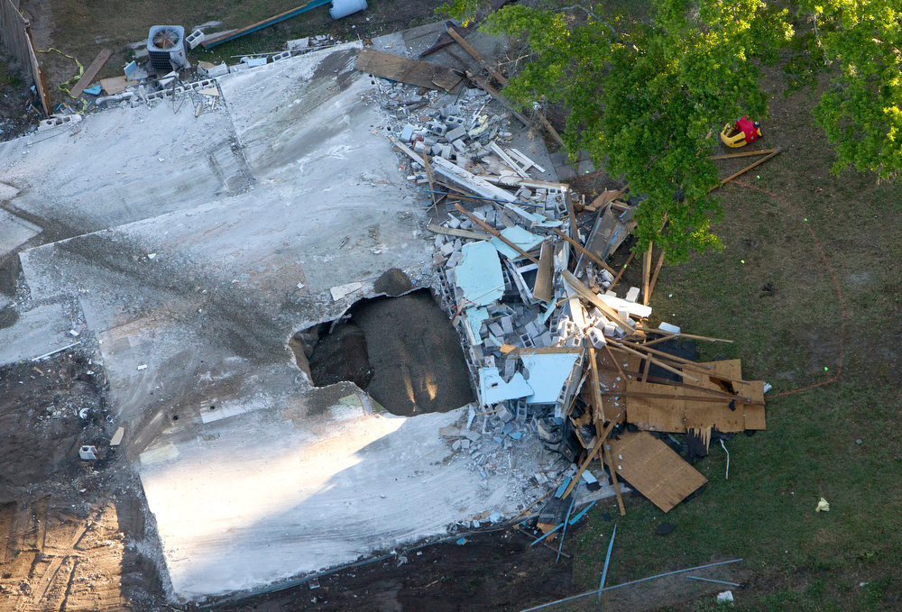 . A giant sinkhole at the home of Jeff Bush, Tuesday, March 5, 2013, in Seffner, Fla.  A huge sinkhole opened up under a bedroom in the home last Thursday, Feb. 28,  and swallowed  Jeff Bush, 37.  Officials gave up hope of finding Bush alive and filled in the hole with crushed rock.  (AP Photo/The Tampa Bay Times, Dirk Shadd)