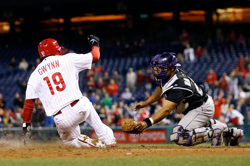 . Philadelphia Phillies\' Tony Gwynn, left, scores past Colorado Rockies catcher Wilin Rosario on a double by Chase Utley during the ninth inning of a baseball game, Wednesday, May 28, 2014, in Philadelphia. Philadelphia won 6-3. (AP Photo/Matt Slocum)