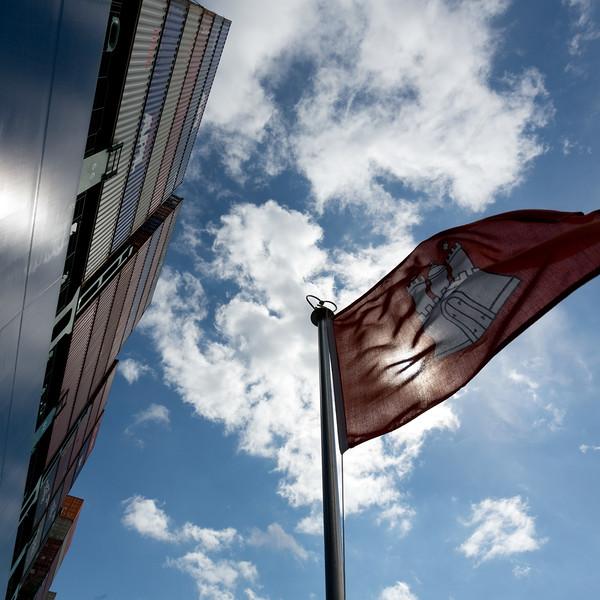 Hamburg Flagge vor blauem Himmel und Containerschiff Schlepper BUGSIER 7