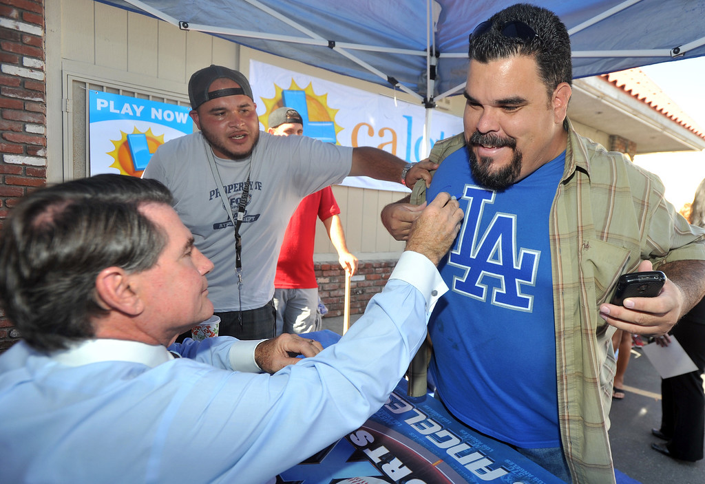 . Former Dodgers first baseman Steve Garvey signs the t-shirt of James Moreno, of Whittier, during a promotion for the California State Lottery\'s new $5M scratchers at the Barley Bin Liquor Store in Whittier on Wednesday October 2, 2013. Fans lined up around the parking lot to get Garvey\'s autograph. (Whittier Daily News/Staff Photo by Keith Durflinger)