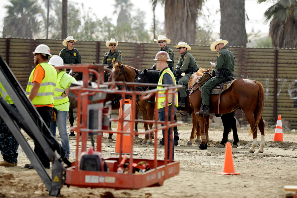 . Border Patrol agents on horseback look on as crews work on border wall prototypes Thursday, Oct. 19, 2017, in San Diego. Companies are nearing an Oct. 26 deadline to finish building eight prototypes of President Donald Trump\'s proposed border wall with Mexico. (AP Photo/Gregory Bull)