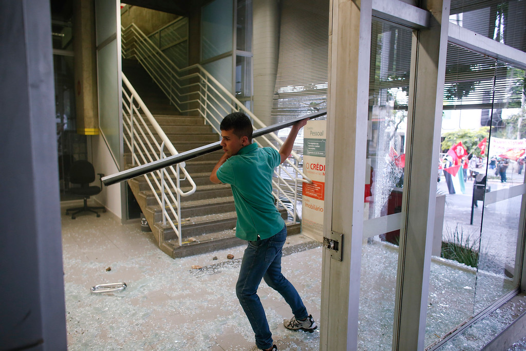 . A protester brakes the window of a bank  during a demonstration against the 2014 World Cup in Belo Horizonte, Brazil, Thursday, June, 12, 2014. (AP Photo/Victor R. Caivano)