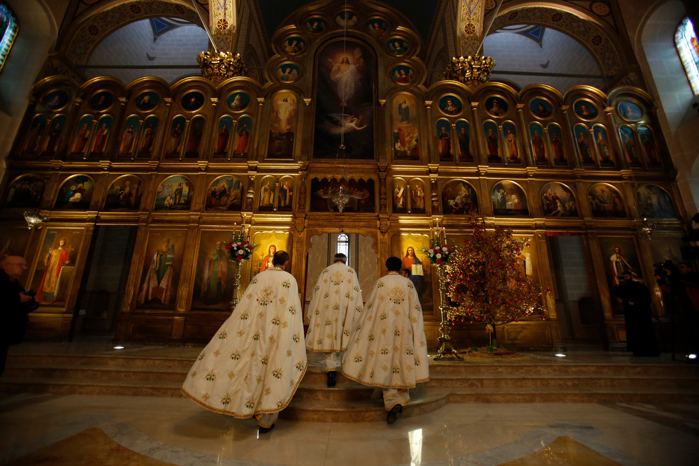. FILE - In this Jan. 7, 2014 file photo, Orthodox priests lead an Orthodox Christmas service at the Bosnian Orthodox church in Sarajevo, Bosnia. World War I is just one era in the history of this multicultural city with its legacies of Islamic Ottoman, Jewish, Christian Orthodox and Roman Catholic religions. (AP Photo/Amel Emric, File)