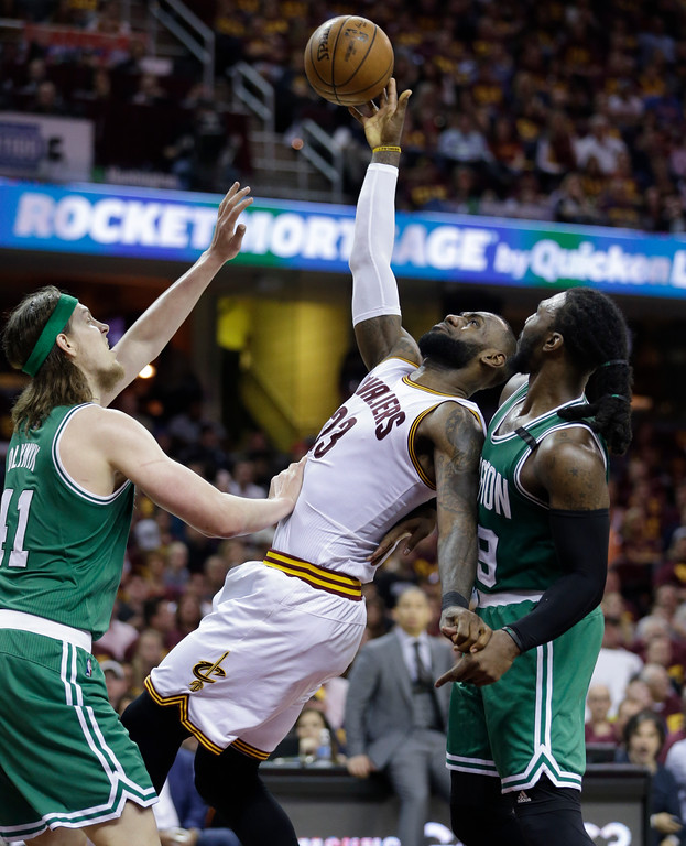 . Cleveland Cavaliers\' Kyrie Irving (23) gets off a shot between Boston Celtics\' Kelly Olynyk (41) and Jae Crowder (99) during the second half of Game 3 of the NBA basketball Eastern Conference finals, Sunday, May 21, 2017, in Cleveland. (AP Photo/Tony Dejak)