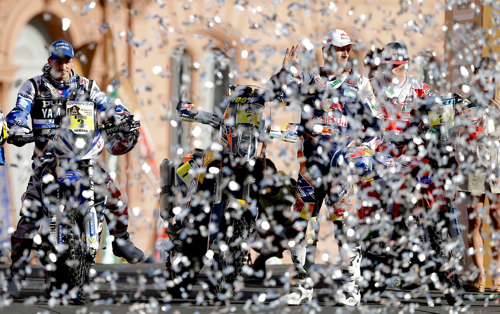 . In this Saturday, Jan. 3, 2015 photo, Honda rider Joan Barreda of Spain, right, KTM rider Marc Coma of Spain, center, and Yamaha rider Olivier Pain of France, left, arrive  at the podium ramp as confetti flies during the symbolic start of the Dakar Rally 2015 in Buenos Aires, Argentina. The race will start on Jan. 4 and finish on Jan. 17, from Buenos Aires, passing through Bolivia and Chile and returning to Argentina.(AP Photo/Natacha Pisarenko)
