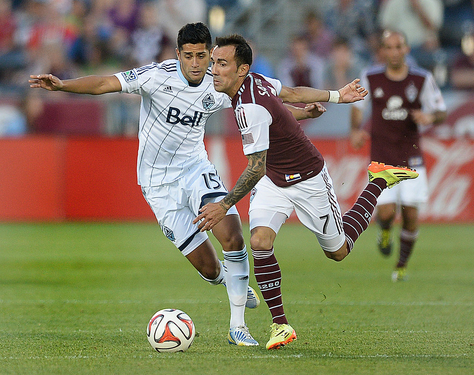 . COMMERCE CITY, CO - JUNE 28: Vancouver midfielder Matias Laba (15) and Colorado forward Vicente Sanchez (7) battled for the ball in the second half. The Colorado Rapids defeated the Vancouver Whitecaps 2-0 at Dick\'s Sporting Goods Park Saturday night, June 28, 2014.  Photo by Karl Gehring/The Denver Post
