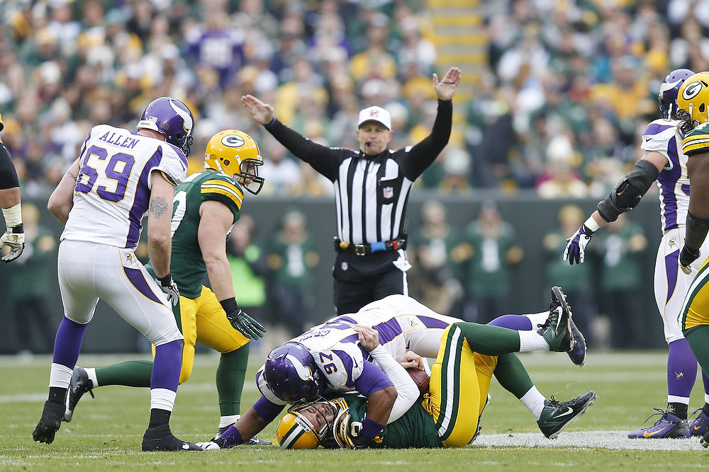 . Aaron Rodgers #12 of the Green Bay Packers gets tackled by Everson Griffen #97 of the Minnesota Vikings during the game at Lambeau Field on December 2, 2012 in Green Bay, Wisconsin. The Packers won 23-14. (Photo by Joe Robbins/Getty Images)