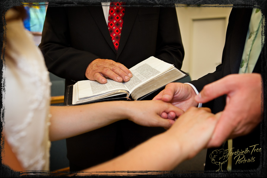 Photo of Chelsea and Tucker holding hands with the preacher holding his bible in the background