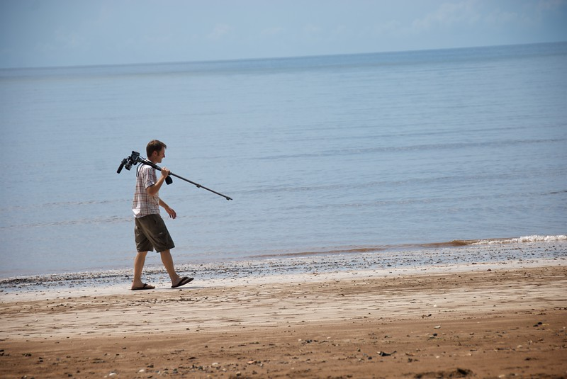 Andy walks along the beach with camera  OFM team