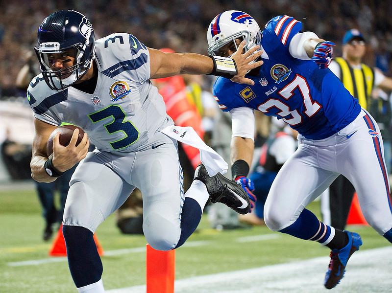 . Seattle Seahawks quarterback Russell Wilson (3) runs the ball into the end zone for a touchdown past Buffalo Bills\' George Wilson (37) during the first half of an NFL football game, Sunday, Dec. 16, 2012, in Toronto. (AP Photo/The Canadian Press, Nathan Denette)