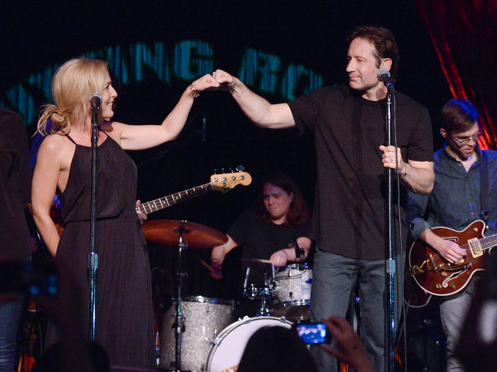 """. David Duchovny and actress Gillian Anderson fist-bump during their performance of Neil Young\'s \""""Helpless\"""" at The Cutting Room on Tuesday, May 12, 2015, in New York. Duchovny performed songs from his debut album \""""Hell Or Highwater.\"""" (Photo by Evan Agostini/Invision/AP)"""