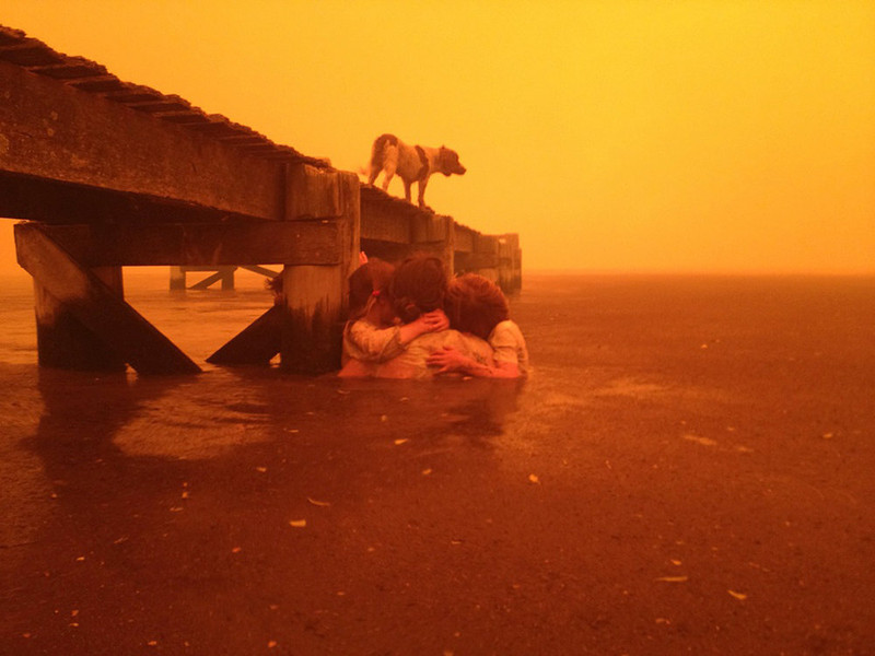 . In this Jan. 4, 2013, photo provided by the Holmes family,  Tammy Holmes and her grandchildren take refuge under a jetty as a wildfire rages nearby in the Tasmanian town of Dunalley, east of the state capital of Hobart, Australia. The family credits God with their survival from the fire that destroyed around 90 homes in Dunalley. Record temperatures across southern Australia cooled Wednesday, Jan. 9, 2013, reducing the danger from scores of raging wildfires but likely bringing only a brief reprieve from the summerís extreme heat and fire risk. (AP Photo/Holmes Family, Tim Holmes)