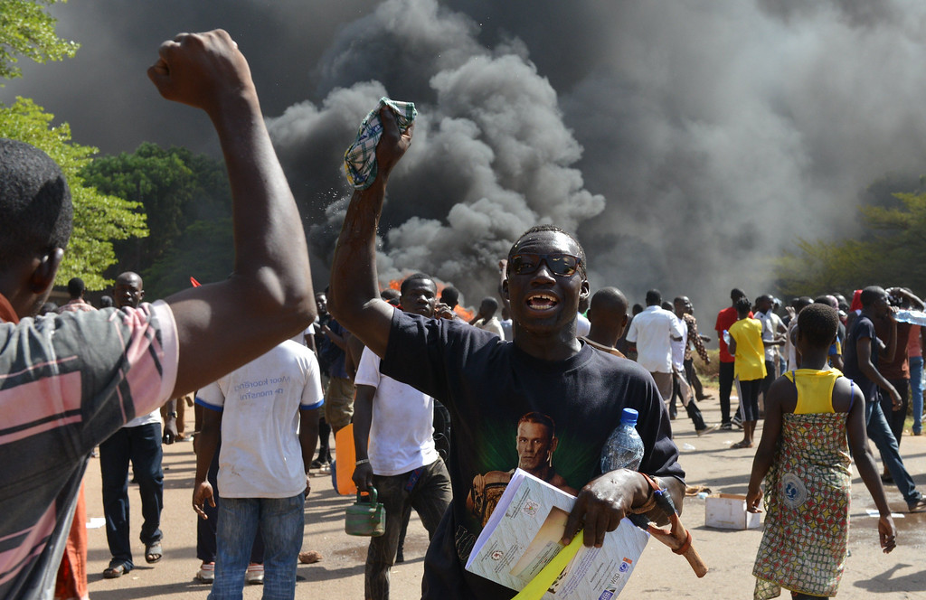 . Burkina Faso protesters gesture outside the parliament in Ouagadougou on October 30, 2014 as cars and documents burn. Hundreds of angry demonstrators in Burkina Faso stormed parliament on October 30 before setting it on fire in protest at plans to change the constitution to allow President Blaise Compaore to extend his 27-year rule. ISSOUF SANOGO/AFP/Getty Images