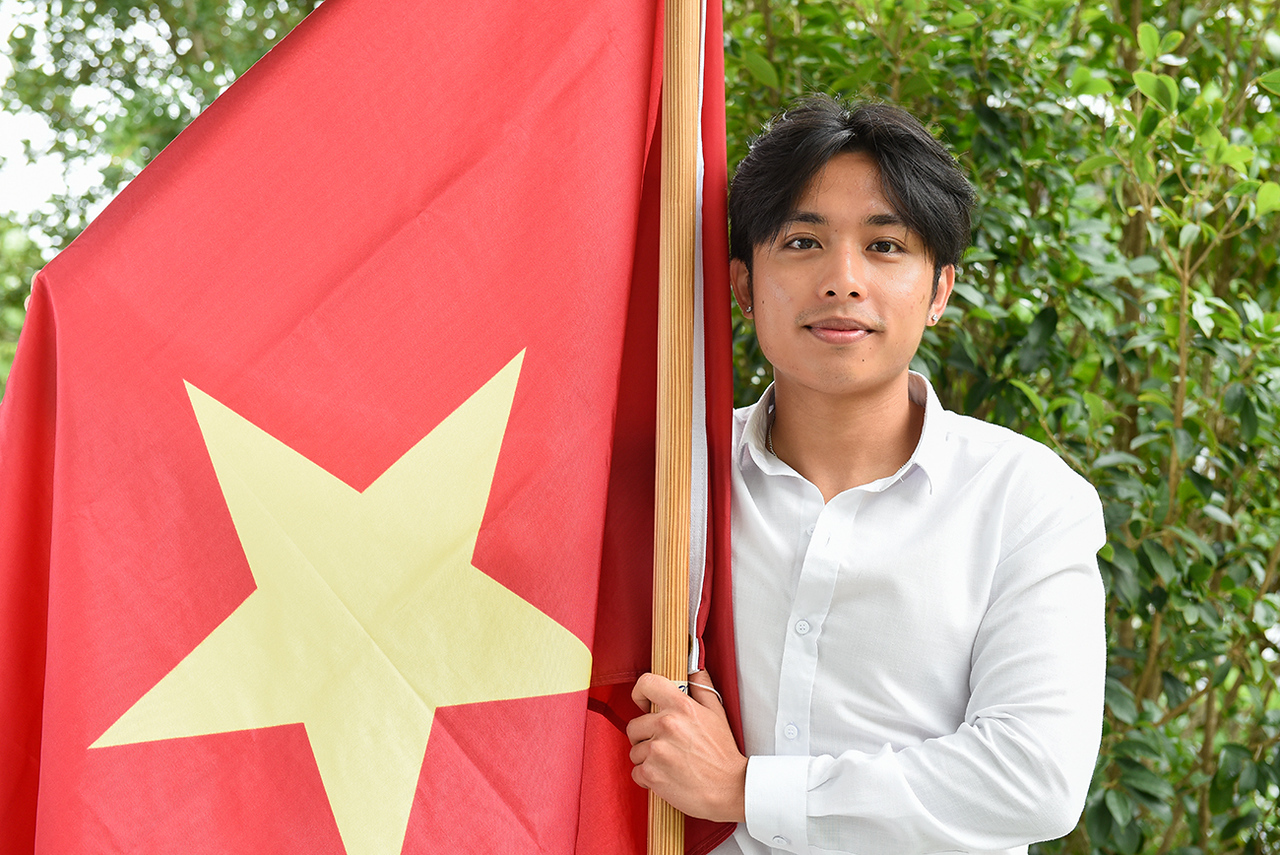 """Hung """"Tommy"""" Nguyen holds the Vietnam flag."""