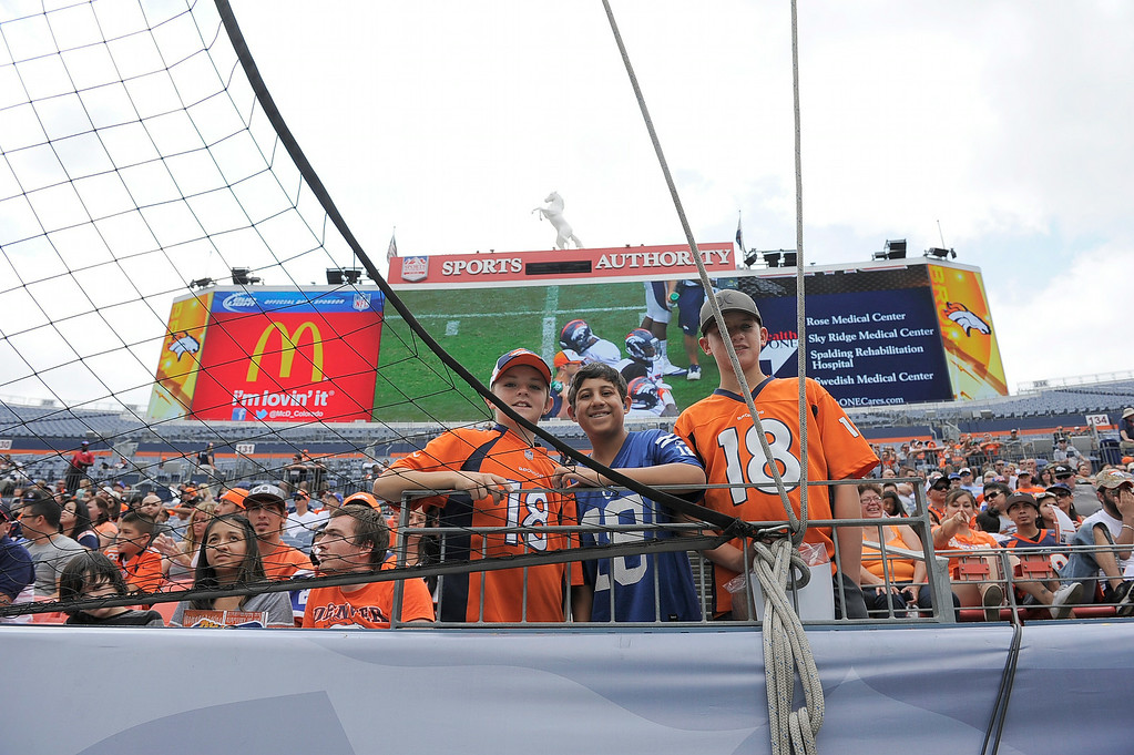 . Denver Broncos fans Kaiden, John Paul and Austin sport their Manning jerseys as they attend day four of the Denver Broncos 2014 training camp July 27, 2014 at Sports Authority Field at Mile High. (Photo by John Leyba/The Denver Post)