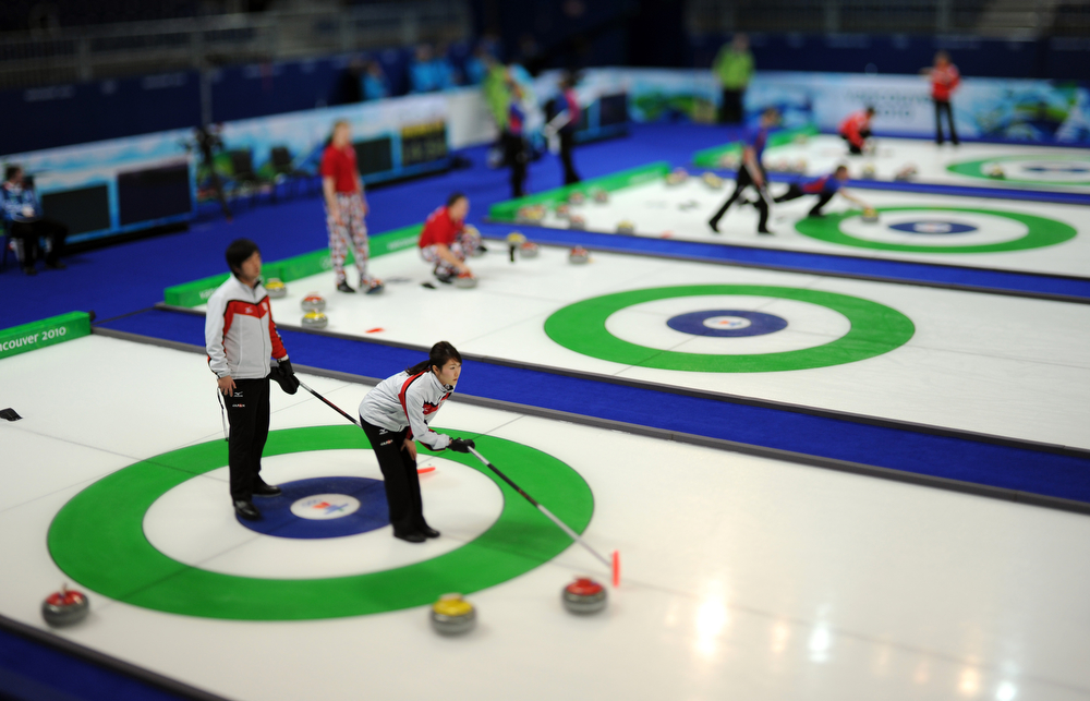 . A member of the Japanese women\'s curling team points to the spot she wants a teammate to aim for during a practice session at the Vancouver 2010 Olympics in Vancouver, British Columbia, Sunday, Feb. 14, 2010. (AP Photo/Robert F. Bukaty)