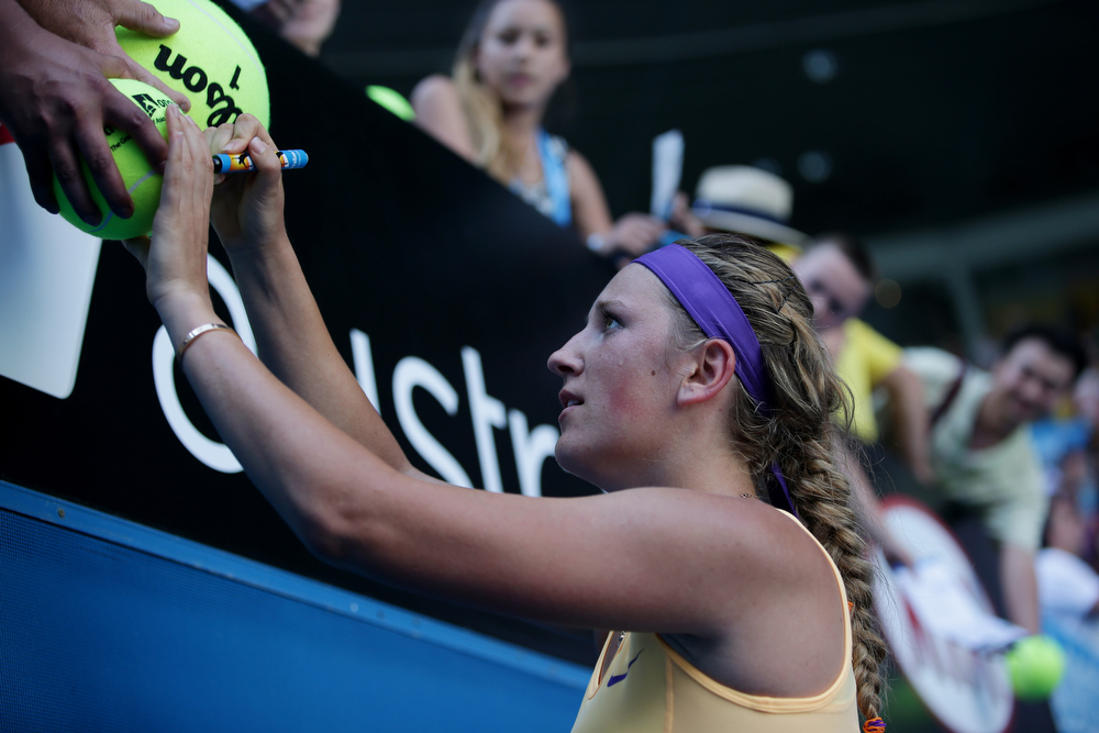 Description of . Victoria Azarenka of Belarus signs autographs after defeating Sloane Stephens of the US in their semifinal match at the Australian Open tennis championship in Melbourne, Australia, Thursday, Jan. 24, 2013. (AP Photo/Aaron Favila)