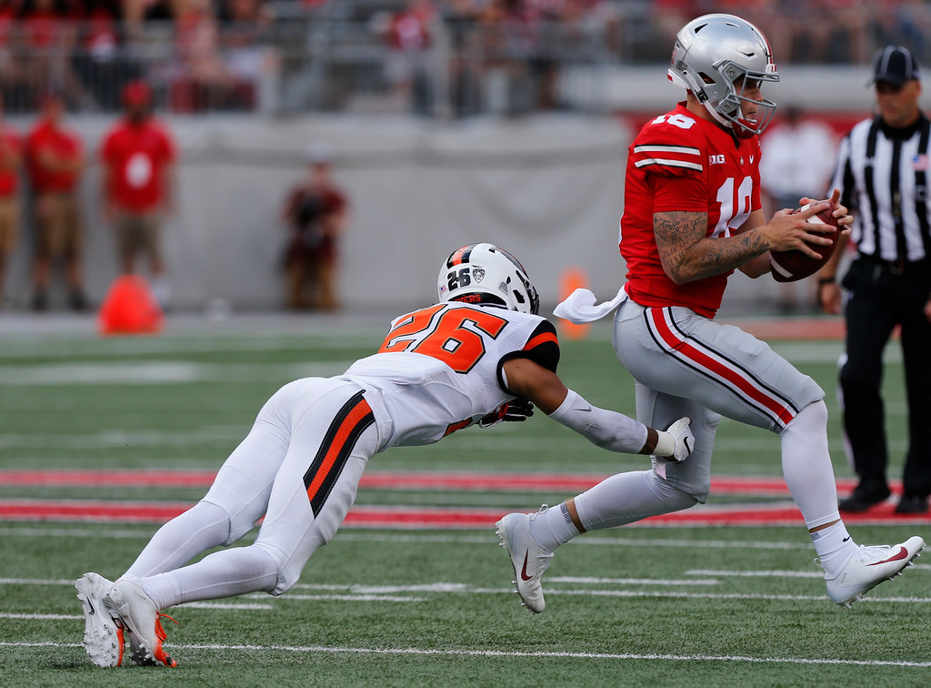 . Oregon State defensive back Jaydon Grant, left, tries to tackle Ohio State quarterback Tate Martell during the second half of an NCAA college football game Saturday, Sept. 1, 2018, in Columbus, Ohio. Ohio State beat Oregon State 77-31. (AP Photo/Jay LaPrete)