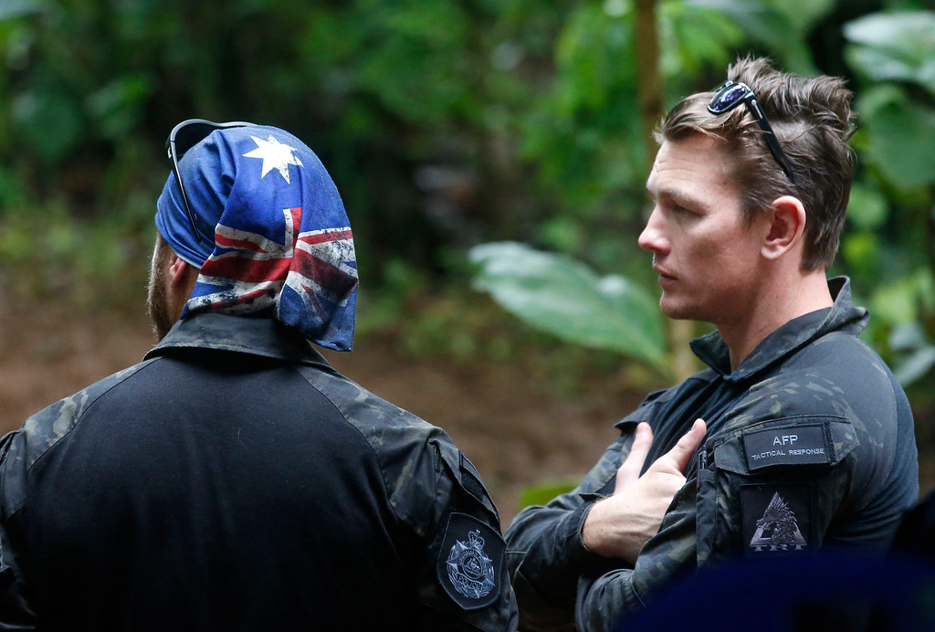 . Australian Federal Police and Defense Force personnel talk each other near a cave complex where 12 boys and their soccer coach went missing, in Mae Sai, Chiang Rai province, in northern Thailand, Sunday, July 1, 2018. The frantic effort to locate them in the cave for a week picked up pace as a break in the rain eased flooding in the system of caverns and more experts from around the world joined the anxious rescue mission. (AP Photo/Sakchai Lalit)