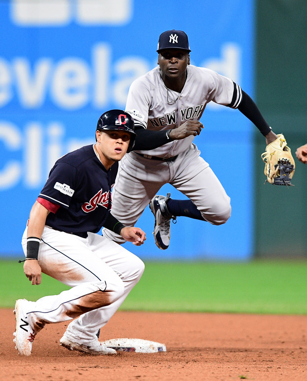 . New York Yankees\' Didi Gregorius, top, forces out Cleveland Indians\' Giovanny Urshela at second base in the fifth inning of Game 5 of baseball\'s American League Division Series, Wednesday, Oct. 11, 2017, in Cleveland. Francisco Lindor was out at first base for the double play. (AP Photo/David Dermer)
