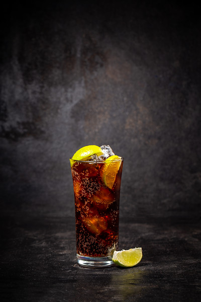 Glass Of Cuba Libre Decorated With Lime On Black Background