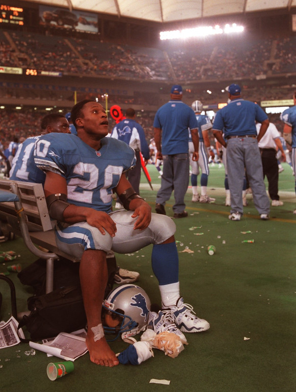 . Lions warrior Barry Sanders watches the game from the bench near the end of the game as he unwraps his ankles and tape from his feet after setting another 100 plus rushing record.