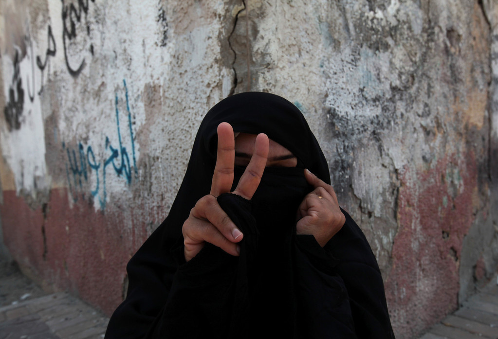 . A Bahraini anti-government protester gestures  during a march in the western village of Malkiya, Bahrain, on Wednesday, Aug. 14, 2013. Opposition groups launched a fresh push against the Gulf monarchy on Wednesday, an effort to revitalize their 2 1/2-year-old pro-democracy uprising. Arabic writing on the wall is a partially obscured call to free prisoners. (AP Photo/Hasan Jamali)