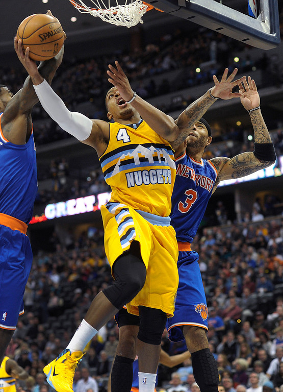 . Denver guard Randy Foye (4) worked under the hoop between New York defenders Iman Shumpert, left, and Kenyon Martin, right, in the second half. Photo By Karl Gehring/The Denver Post