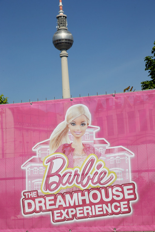 . A banner advertises the Barbie Dreamhouse Experience as the broadcast tower at Alexanderplatz stands behind on May 16, 2013 in Berlin, Germany. The Barbie Dreamhouse is a life-sized house full of Barbie fashion, furniture and accessories and will be open to the public until August 25 before it moves on to other cities in Europe.  (Photo by Sean Gallup/Getty Images)