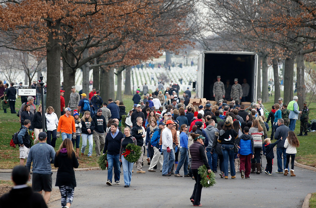 . A crowd of volunteers gathers around a truck to get wreaths to place at graves as part of Wreaths Across America at Arlington National Cemetery, Saturday, Dec. 12, 2015 in Arlington, Va. Organizers estimated that volunteers placed 240,815 wreaths at Arlington. (AP Photo/Alex Brandon)