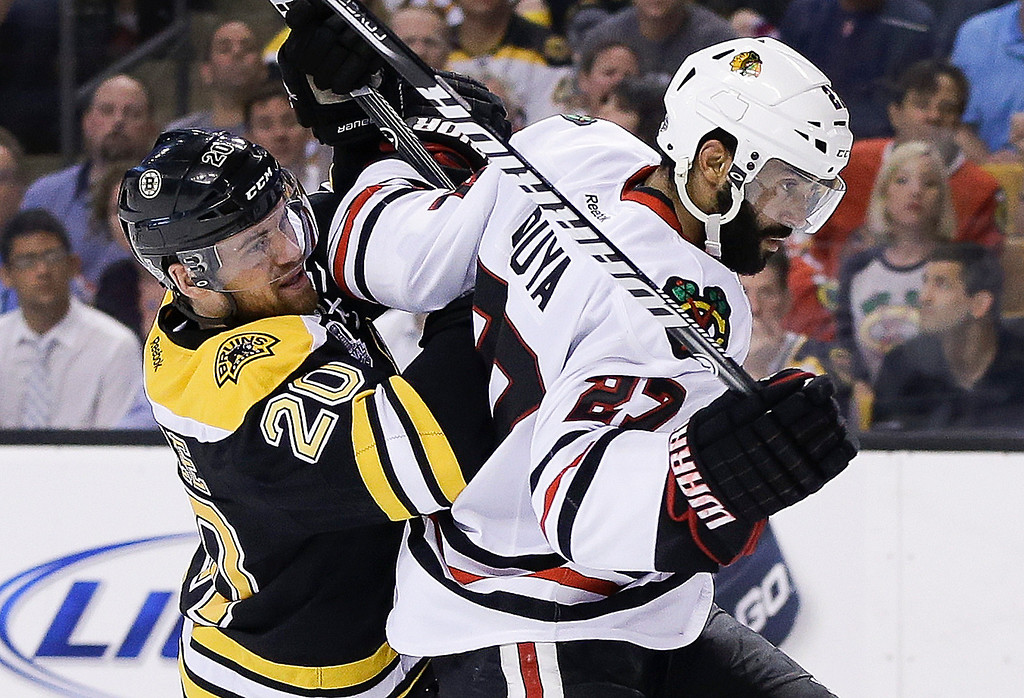 . Boston Bruins left wing Daniel Paille (20) checks Chicago Blackhawks defenseman Johnny Oduya (27), of Sweden, during the second period in Game 6 of the NHL hockey Stanley Cup Finals Monday, June 24, 2013 in Boston. (AP Photo/Elise Amendola)