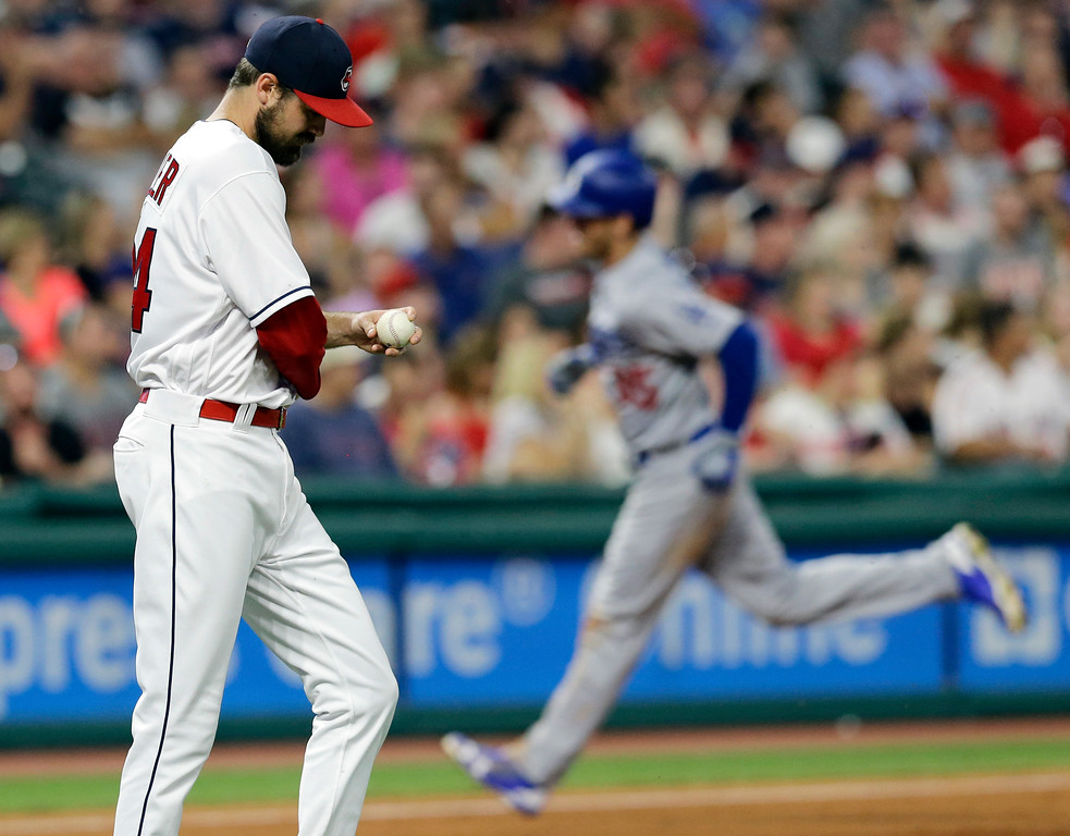 . Cleveland Indians relief pitcher Andrew Miller, left, waits for Los Angeles Dodgers\' Cody Bellinger to run the bases on a solo home run during the eighth inning of a baseball game, Tuesday, June 13, 2017, in Cleveland. (AP Photo/Tony Dejak)