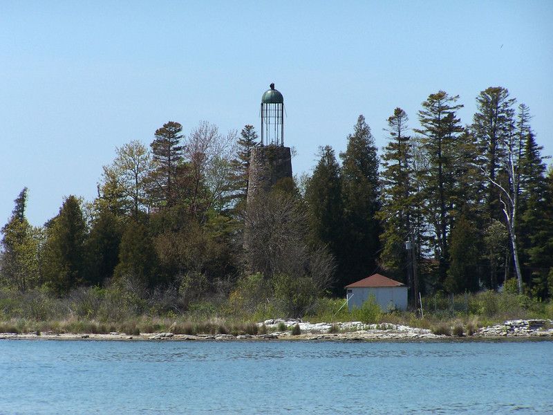 Baileys Harbor's Old Birdcage Lighthouse was built by Mr. Alison Sweet. Selecting a one thousand foot by two hundred and fifty foot island as the best location for the tower, Sweet's crew began construction in 1852. With lake levels extremely low that year, they were able to transport all the building materials directly to the island. Built of native stone from Sweet's quarry, the fifty-two foot tower was capped with a birdcage-style lantern room, and equipped with a fixed white  Sixth Order Fresnel lens. As was usual in lantern rooms of this style, the lens was supported in the center of the tower with no platform or catwalk surrounding the lantern room. The lens was later upgraded to a fixed white  Fifth Order Fresnel in 1858.