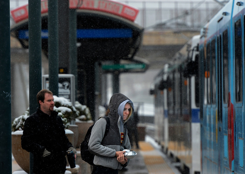 . Commuters board a train at the light rail station in downtown in Littleton, CO April 09, 2013. A winter storm has blown into northeastern Colorado, with strong winds and below-freezing temperatures creating blizzard-like conditions at times. (Photo By Craig F. Walker/The Denver Post)