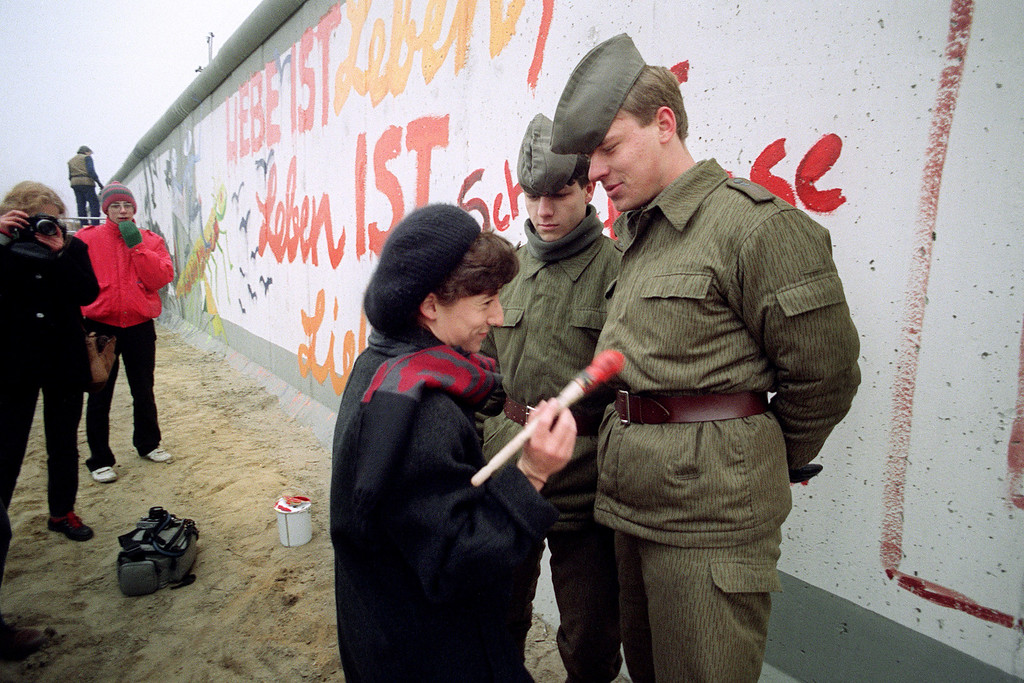 """. An East German artist offers to paint Vopos\' uniforms trying to prevent her from going on painting on the Berlin Wall, on November 21, 1989 in Berlin. On November 09, Gunter Schabowski, the East Berlin Communist party boss, declared that starting from midnight, East Germans would be free to leave the country, without permission, at any point along the border, including the crossing-points through the Wall in Berlin. The Berlin concrete wall was built by the East German government 13 August 1961 to seal off East Berlin from the part of the city occupied by the three main Western powers to prevent mass illegal immigration to the West. According to the \""""August 13 Association\"""" which specialises in the history of the Berlin Wall, at least 938 people - 255 in Berlin alone - died, shot by East German border guards, attempting to flee to West Berlin or West Germany. The wall was opened 09 November 1989 and has been demolished since then.        (Photo credit should read PATRICK HERTZOG/AFP/Getty Images)"""