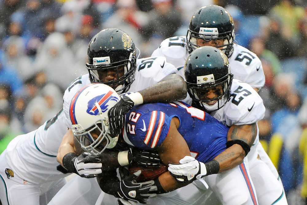 . Buffalo Bills\' Fred Jackson (22) is tackled by Jacksonville Jaguars\' Dwight Lowery (25), George Selvie (91), and Paul Posluszny (51) during the first half of an NFL football game Sunday, Dec. 2, 2012 in Orchard Park, N.Y. (AP Photo/Gary Wiepert)
