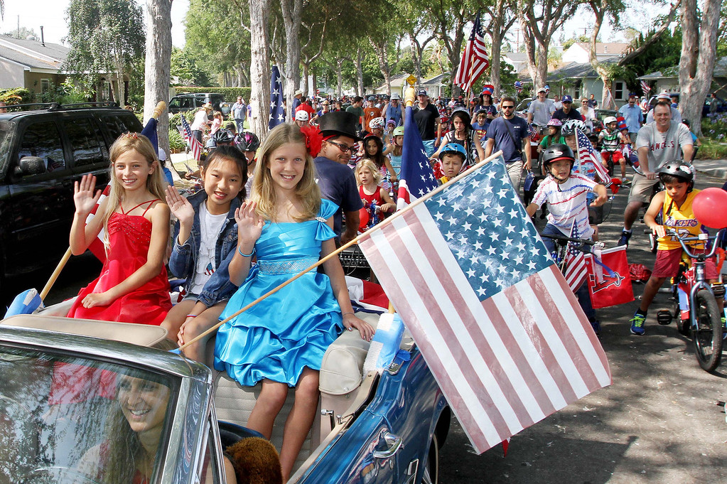 . July 4, 2013-Photo by Tracey Roman/for the Press-Telegram  Malerie Hurley, Alex Lam, and Allie Stone, lead off the annual bike parade through the streets of East Long Beach Thursday morning.