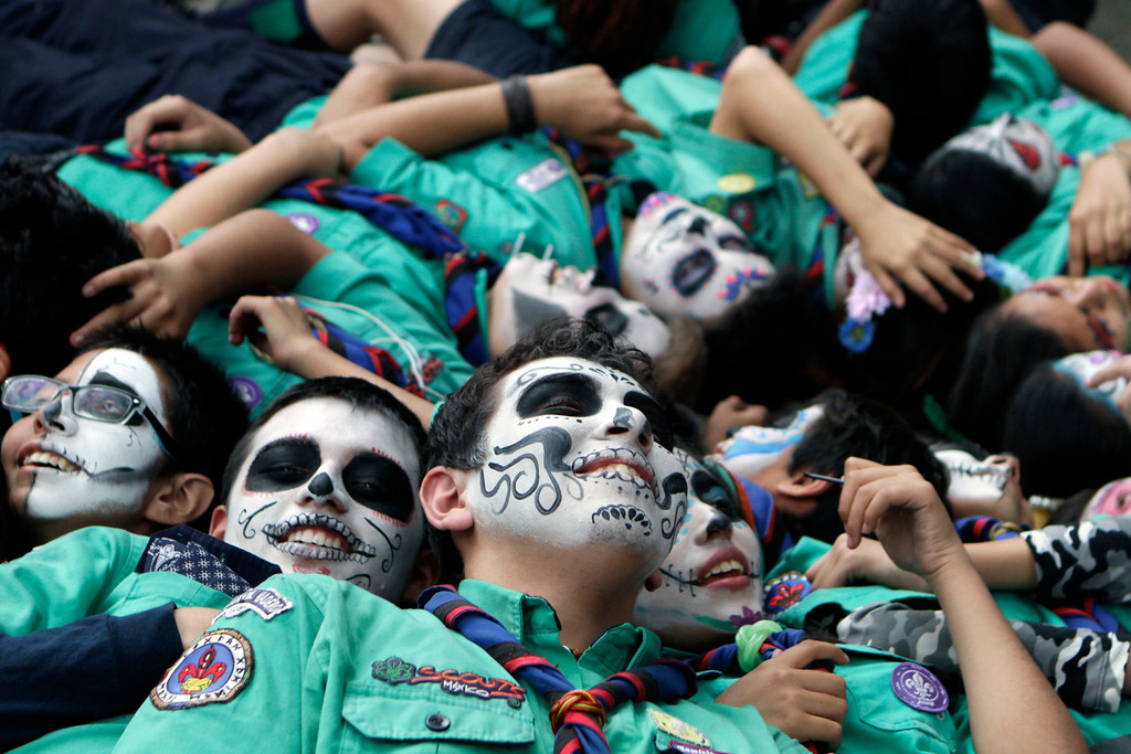 . Members of the Gustavo Madero scout troop, with their faces painted as calaveras, lie down on a sidewalk for a group photo as they wait for the start of the Gran Procession of the Catrinas, to mark the upcoming Day of the Dead holiday, in Mexico City, Sunday, Oct. 23 2016. The gran procession is one of many that will take place in Mexico City as part of the celebrations, culminating with visits to the graves of departed loved ones on Nov. 1 and 2. The figure of a skeleton wearing broad-brimmed hat was first done as a satirical engraving by artist Jose Guadalupe Posada sometime between 1910 and his death in 1913, to poke fun at women who pretended to be European by dressing elegantly and as a critique of social stratification. (AP Photo/Anita Baca)