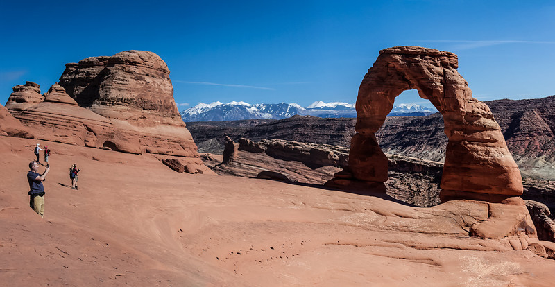 hikers take photos of Delicate Arch and snow topped Rockies