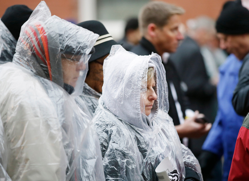 . People wearing rain ponchos gather at security before a ceremony to mark the 50th anniversary of the assassination of John F. Kennedy, Friday, Nov. 22, 2013, at Dealey Plaza in Dallas. President Kennedy\'s motorcade was passing through Dealey Plaza when shots rang out on Nov. 22, 1963. (AP Photo/Tony Gutierrez)