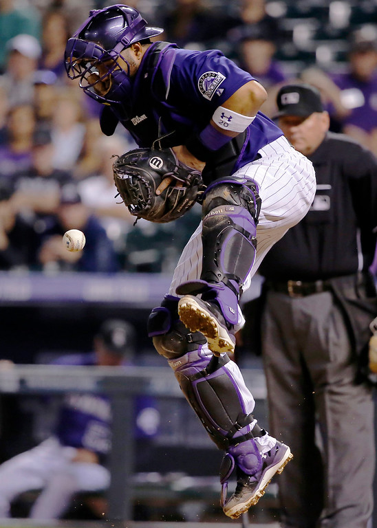 . Colorado Rockies catcher Wilin Rosario jumps to block a throw to home against the Los Angeles Dodgers during the sixth inning of a baseball game Monday, Sept. 15, 2014, in Denver. (AP Photo/Jack Dempsey)