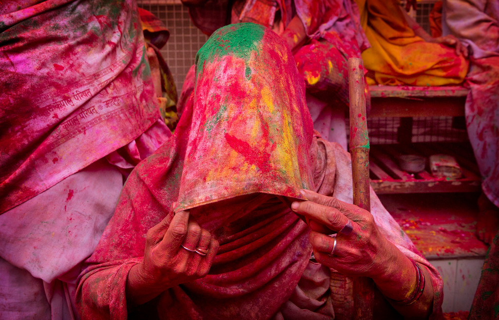 . An Indian widow smeared with colours covers her face during Holi celebrations, the arrival of spring festival at the Gopinath temple in Vrindavan, 180 kilometers (112 miles) south-east of New Delhi, India, Thursday, March 9, 2017. Up to just a few years ago this joyful celebration was forbidden for Hindu widows. Like hundreds of thousands of observant Hindu women, they would have been expected to live out their days in quiet worship, dressed only in white, with their very presence being considered inauspicious for all religious festivities. (AP Photo /Manish Swarup)