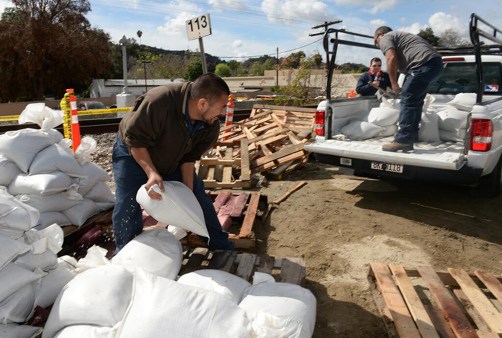 . Filiberto Castaneda, left, and Eric Morones load up sandbags at the Glendora City Yard for St. Dorothy\'s School in Glendora on Thursday February 27, 2014. (Staff Photo by Keith Durflinger/San Gabriel Valley Tribune)