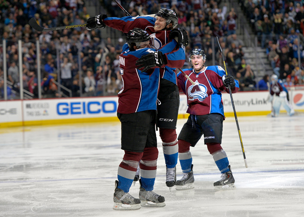 . Colorado Avalanche center Nathan MacKinnon (29) jumps on Nate Guenin (5) as Tyson Barrie (4) cheers following Guenin\'s goal against the Phoenix Coyotes while during the third period of an NHL hockey game on Friday, Feb. 28, 2014, in Denver. (AP Photo/Jack Dempsey)