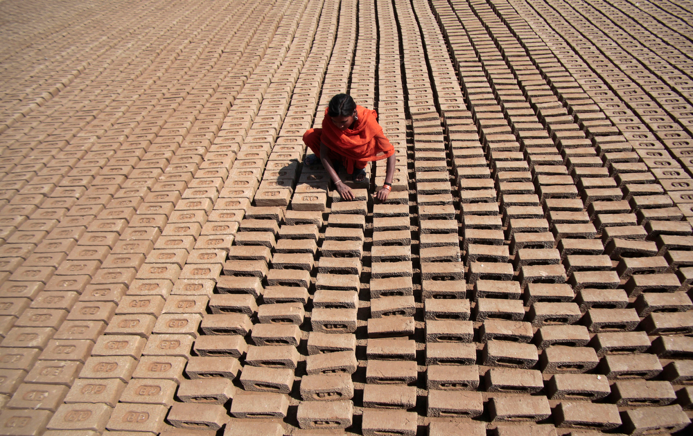 . An Indian woman laborer works at a brick factory on International Women\'s Day on the outskirts of Jammu, India, Saturday, March 8, 2014. (AP Photo/Channi Anand)