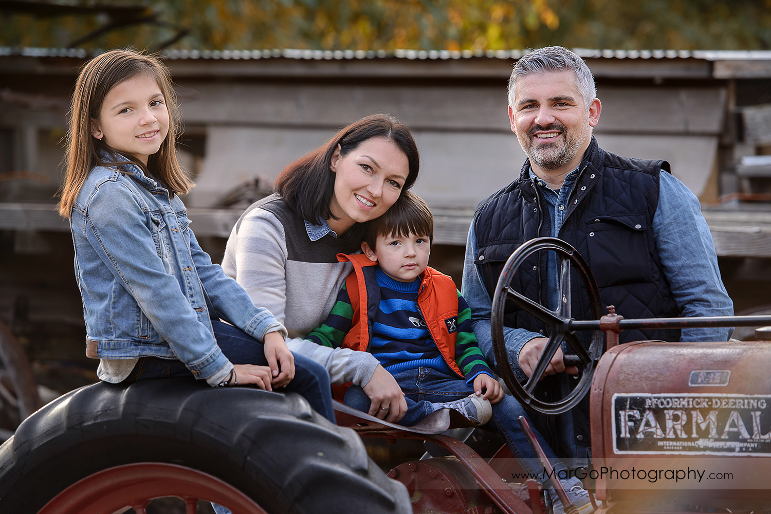 family of 4 in blue and grey clothes sitting on the rusty tractor during photo session at Old Borges Ranch in Walnut Creek