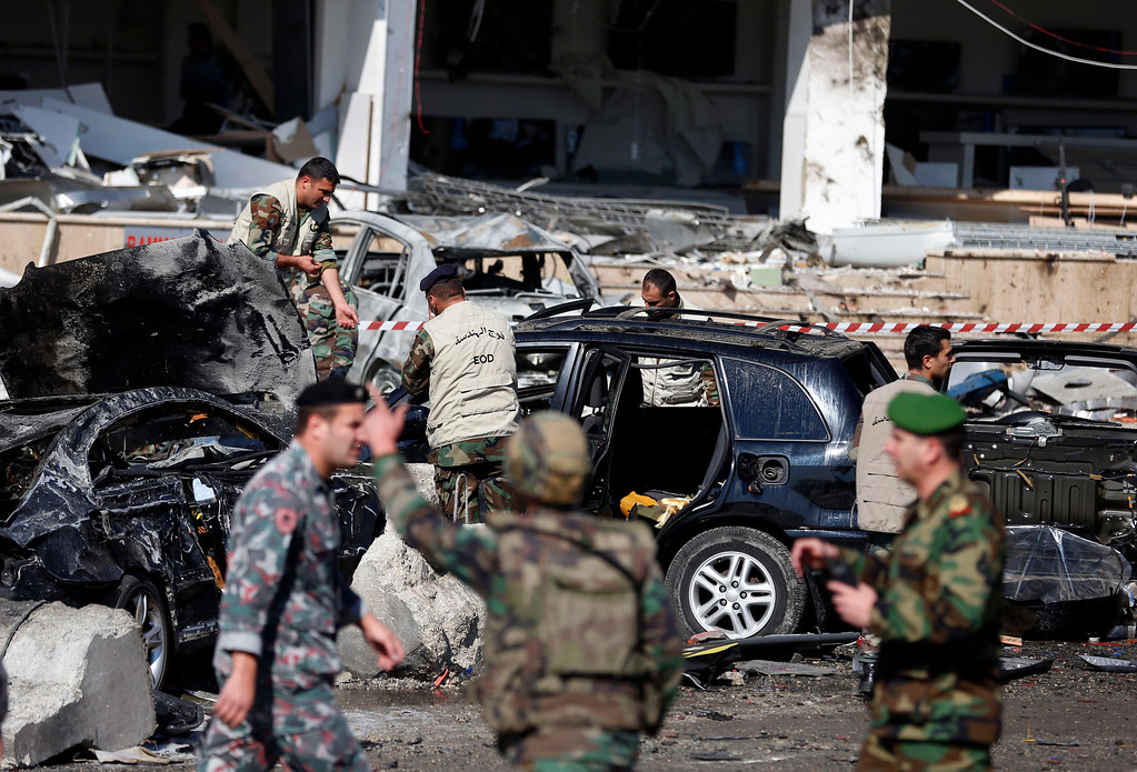 . Lebanese army investigators gather next to burned and damaged cars at the site of explosions, in the suburb of Beir Hassan, Beirut, Lebanon, Wednesday, Feb. 19, 2014.  (AP Photo/Hassan Ammar)